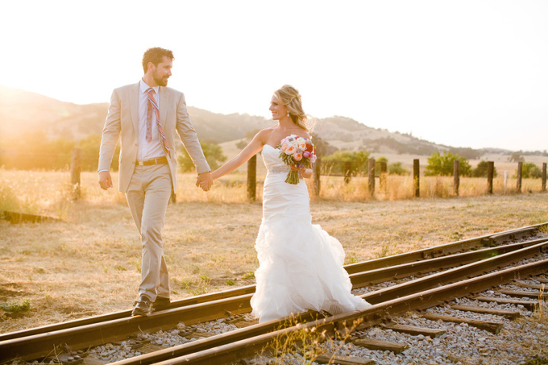 A couple just married at the Santa Margarita Ranch walk on the train tracks at sunset