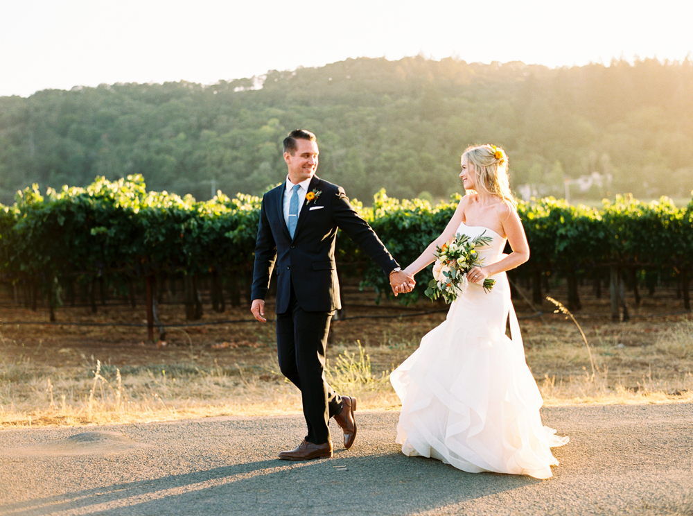 Just married and walking hand in hand at sunset.