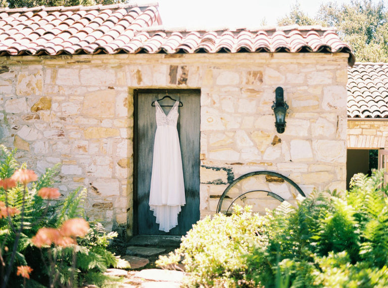 Made With Love bridal dress hanging in rustic doorway