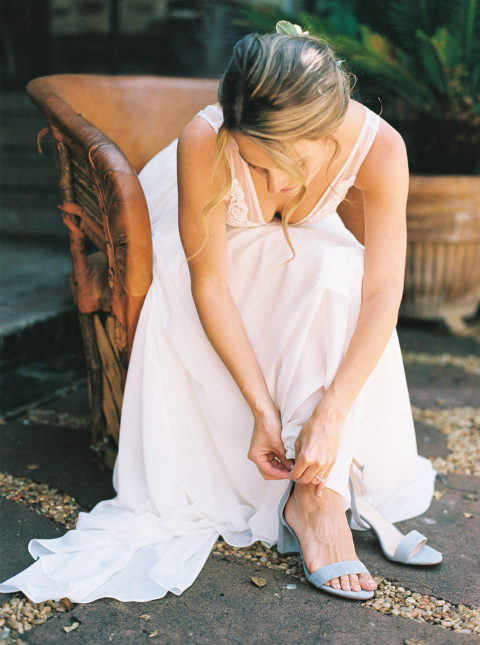 Aly strapping her blue wedding shoes to her ankle