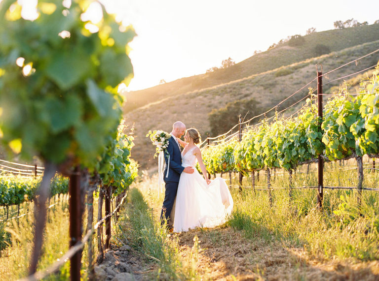Newlyweds Jack and Aly in the vineyards during sunset at Holman Ranch