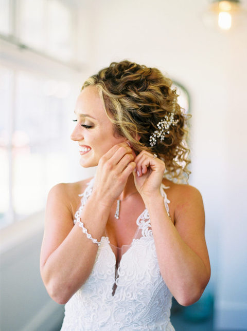 Whitney puts on her earrings in the bridal suite at Mattei's Tavern in Los Olivos