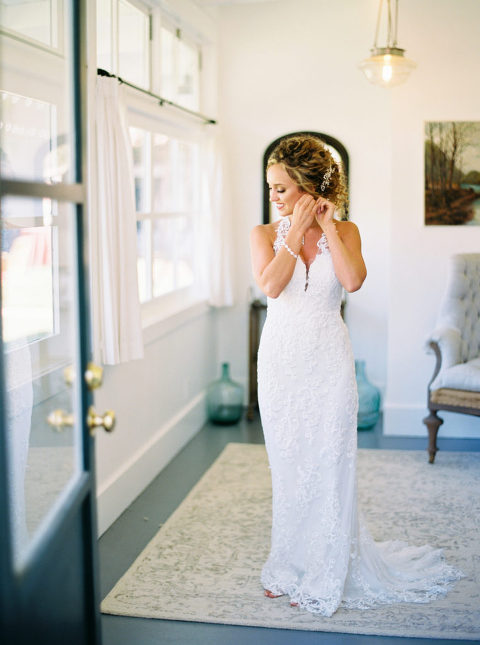 Bride putting on her earrings wearing a Willowby by Watters dress
